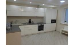 Современная  кухня с крашеными фасадами и проходной ручкой